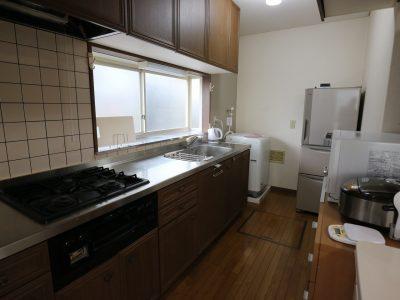 2F:大きな3口コンロの付いているシステムキッチンの向こうに専用の洗濯機と冷蔵庫があります。