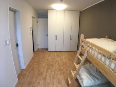 居室約8.4帖。奥にあるのが可動間仕切り収納。2段ベッドもあります。